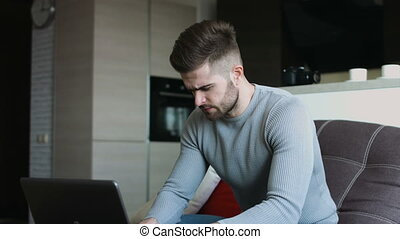 Sexy handsome man using his laptop resting at his fancy apartment .