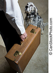 Leaving - Man holding an old suitcase preparing to leave as...