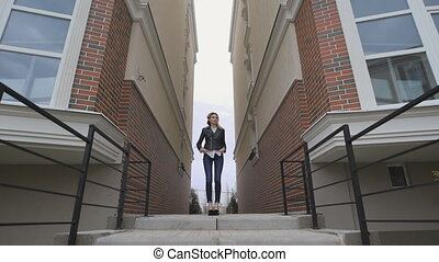 Beautiful thoughtful blond woman stands between two houses....