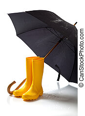 Yellow rainboots and black umbrella on white - A pair of...