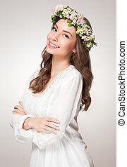 Spring beauty wearing flower wreath. - Portrait of a young...