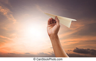 hand preparing to throwing paper plane to mid air againt...