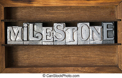 milestone word made from metallic letterpress type on wooden...