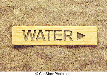 Water direction sign in dry desert sand, guide signpost for...