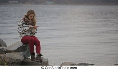 The woman is sitting on the stone located on the coastline...