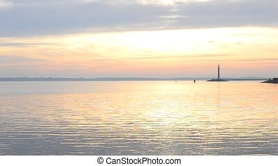 Water landscape with lighthouse and sky during daybreak -...