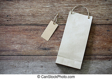 Price tag and paper shopping bag on wooden background