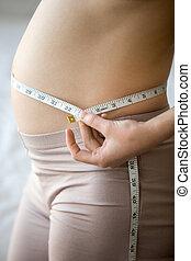Prenatal weight control concept - Close-up of torso of young...