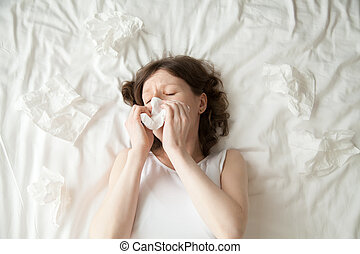 Young woman sneezing into tissue - Young depressed or sick...