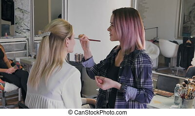 Make-up artist work on her friend Real people beauty salon,...