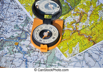 Compass on the map - Orange compass mirror cover lies on...