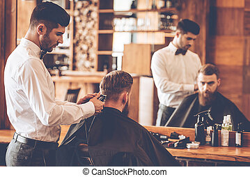 Nape trim. Rear view of young bearded man getting haircut by...