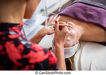 Beautician Applying Facial Mask On Woman's Face