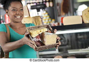 Happy Woman Showing Basket Full Of Cheese And Meat In...