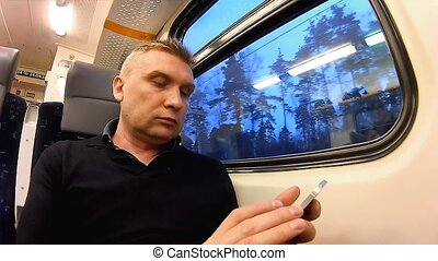 Man uses a smartphone in a compartment of a passenger train...