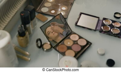 Desk in a beauty salon. reflected in the mirror of her compact face of the girl. Professional Stylist
