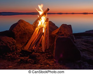 Campfire on the beach at night - Fire and flames of...