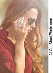 Businesswoman calling over the phone - Close-up portrait of...
