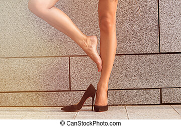 Low view of womans legs isolated on brick wall backround...