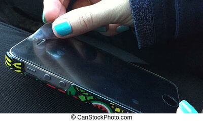 Female fingers with manicure remove a protective film from...
