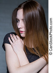 Feeling so lonely - Shot of a young woman embracing herself