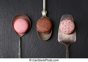 Macarons are on the cutlery, black background. - French...