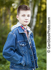 Young boy stands park meadow sunny day, jeans jacket, shirt...