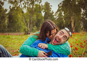 Young couple sitting on the grass in a field of red poppies. The girl kiss the guy while he has a silly smile.