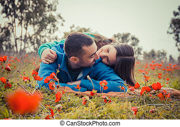Young couple lying on the grass in a field of red poppies and smiling at each other