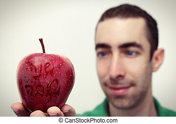 Shana Tova Happy New Year - Man looking at red apple that...