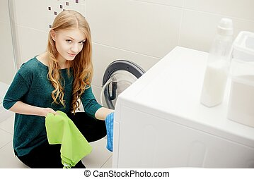 Blond woman put dirty clothes in the washing machine On the...