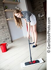 Portrait Of Young Blonde Woman Mopping Floor