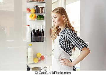 Woman with open refrigerator. she wonders what to pull. You...