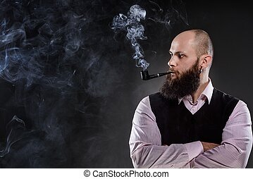 Bald bearded man smoking a pipe. A lot of smoke on the...