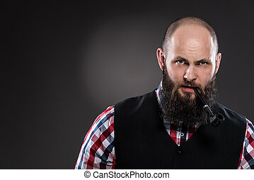 Bearded man in a checkered shirt smoking a pipe on a gray...