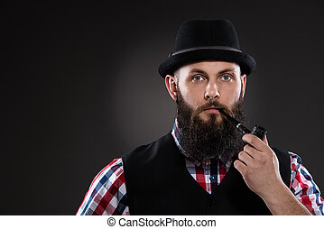 Bearded man in a checkered shirt and a hat smoking a pipe