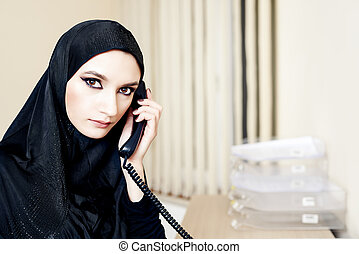 Muslim woman talking on a landline phone at the office