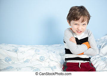 Cute 6 year old boy sitting on the edge of the bed happy...