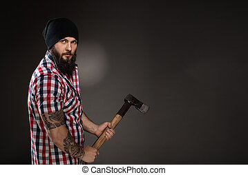 Serious bearded woodcutter holding an axe - Muscular...