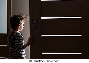 Little boy opens the door to the room by night