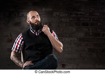 Thoughtful bearded man in a checkered shirt smoking a pipe...