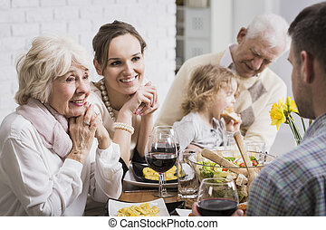 Family is all we have... - Happy family sitting beside table...
