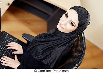 Muzu?ma?ska kobieta siedz?ca na biurowym krze?le i pracuj?ca...