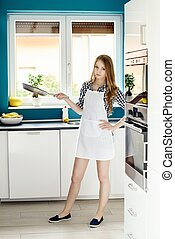 Young beautiful woman posing in the kitchen with a frying...