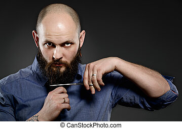 Young hipster man cutting his beard with scissors - grey background