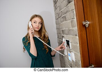 A beautiful young blond woman talking on the intercom in the...