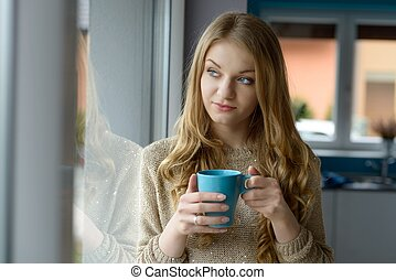 Beautiful blond woman drinking coffee or other drink by the...