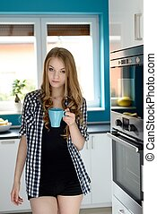 Happy blonde woman holding a cup of coffee in her kitchen