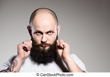 bearded man touching his beard - grey background