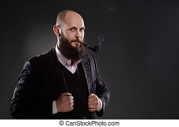 Bald bearded man holding a smoking pipe in his mouth. He is...